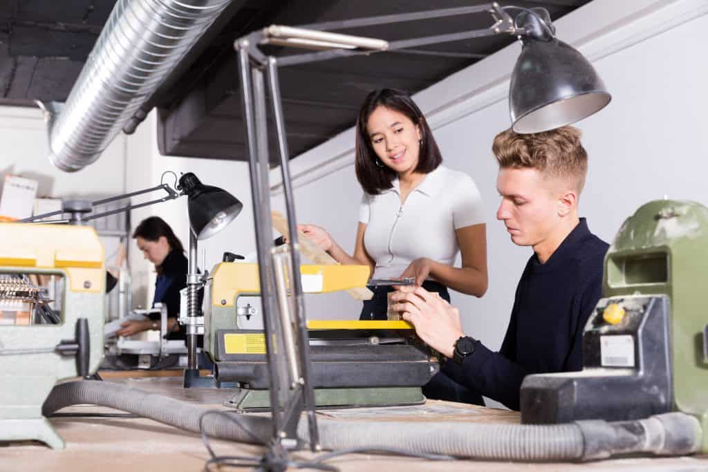 Young female architect helping male colleague making elements on scroll saw